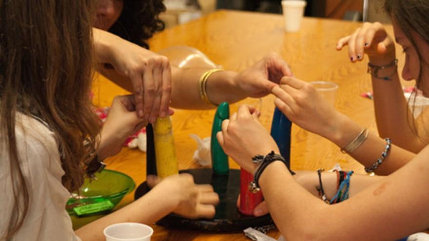 Jóvenes aprender a poner un condón durante un talller sobre sexualidad.