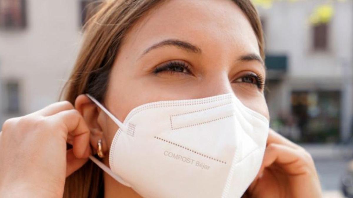 Una mujer utilizando una mascarilla compostable.