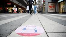 Una señal que pide distancias de dos metros entre personas en una calle de Estocolmo.