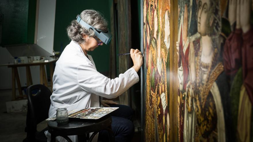 La restauradora Pilar Camón repasa el color del borde de una de las tablas de Blesa.