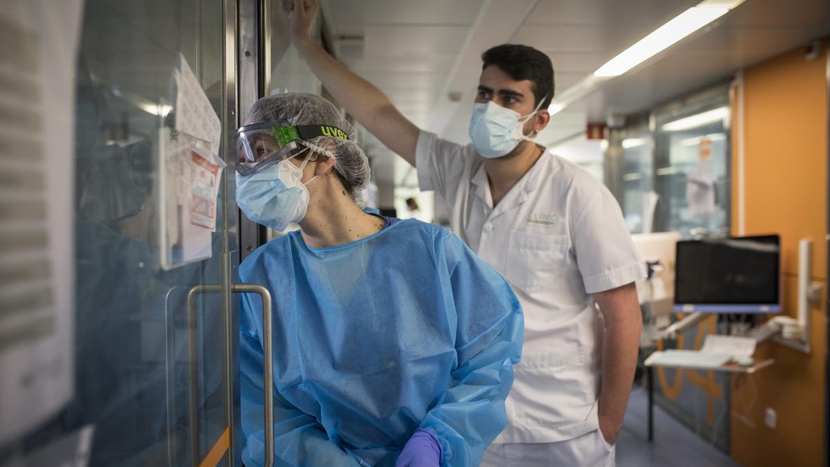 Dos sanitarios miran a través de la ventana de una UCI