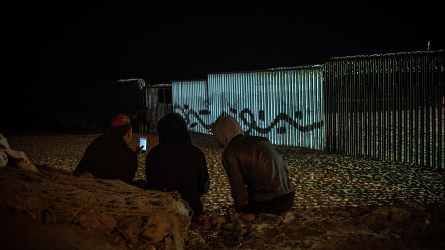 Integrantes de la caravana migrante frente al muro con EEUU.