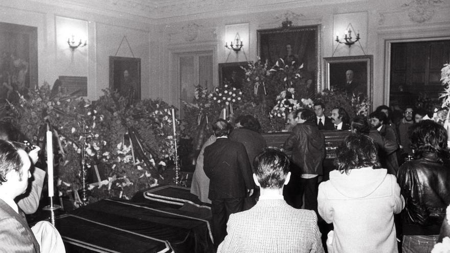 """CAPILLA ARDIENTE DE LOS ABOGADOS ASESINADOS EN MATANZA DE ATOCHA Madrid, 26-1-1977.- Se ha instalado en la sede del colegio de Abogados, en el Palacio de Justicia, la capilla ardiente con los féretros de los abogados asesinados en el despacho laboralista que Comisiones Obreras tiene en la calle Atocha. El pasado 24 de enero nueve personas eran ametralladas por dos jóvenes armados con """"Mariettas""""(Ingram M-10). Los abogados Enrique Valdevira, Luis Javier Benavides y el administrativo Ángel Rodríguez Leal murieron en el acto; Javier Sauquillo y Serafín Holgado en el hospital."""