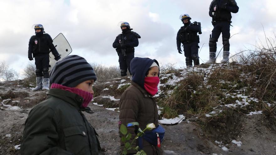 Dos niños pequeños en el campamento de refugiados de Calais, ante la mirada de unos policías.