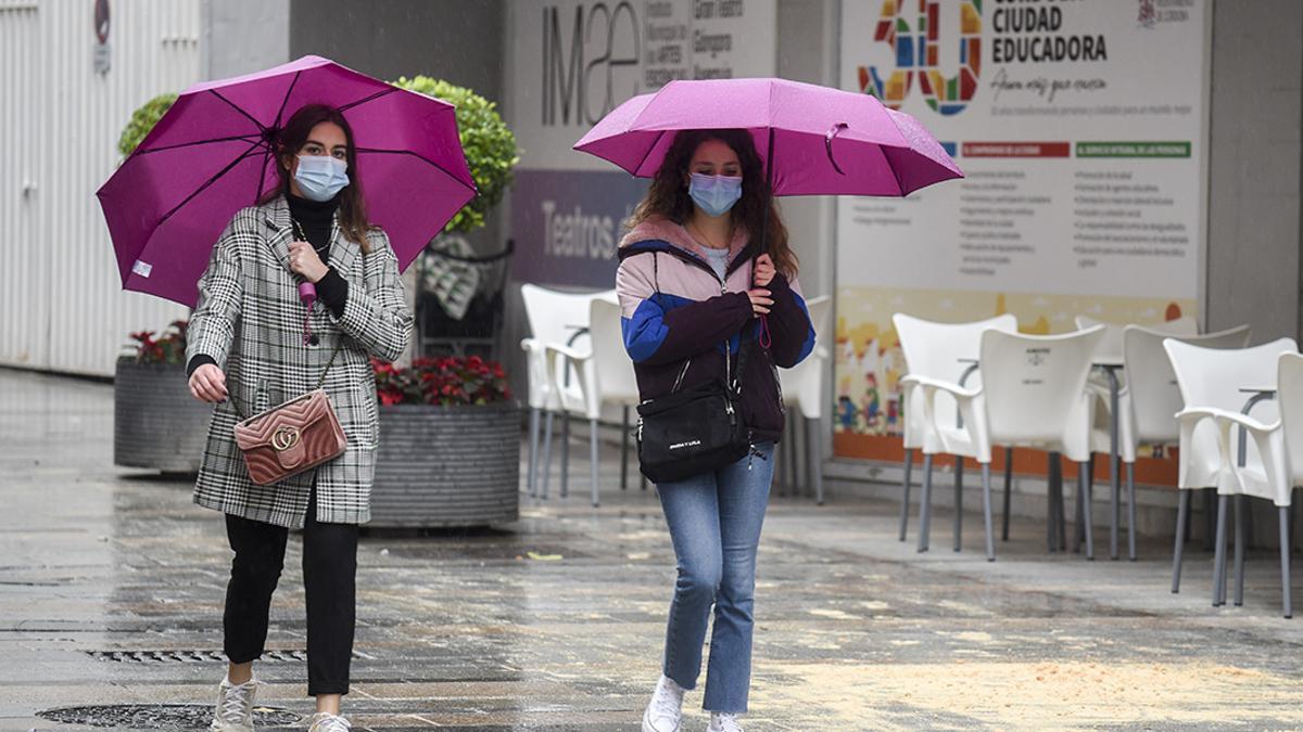 Dos mujeres se protegen de la lluvia con paraguas.