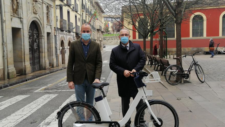 Fermín Alonso y Enrique Maya con una de las bicicletas del nuevo servicio del Ayuntamiento de Pamplona