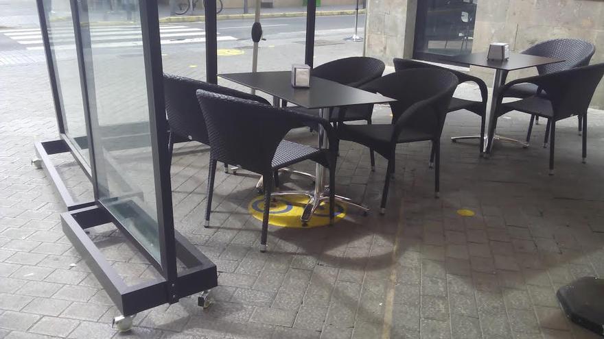 Carril bici bajo las mesas de una terraza.