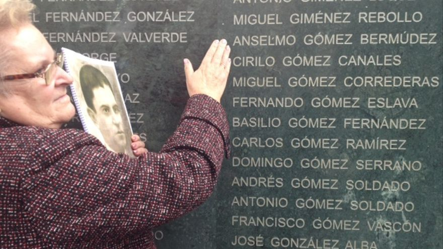 Guillermina Gómez, con la foto de su padre, junto al Muro de la Memoria que recuerda a las víctimas del franquismo.