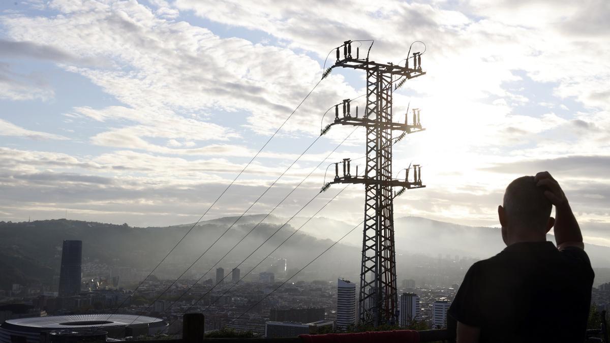 Una persona observa el cableado con el que red eléctrica transporta la energía