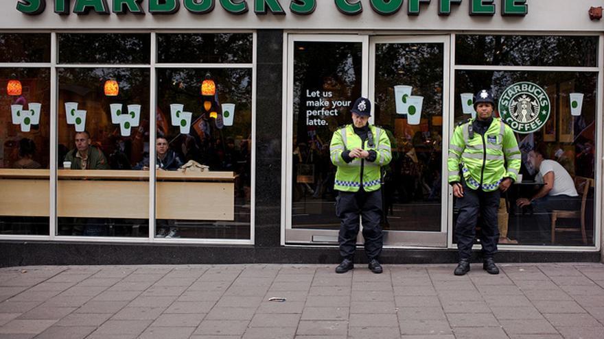 Policías británicos protegen un local de Starbucks durante una manifestación contra la austeridad en Londres. Foto: Flickr de Chris Brown CC.