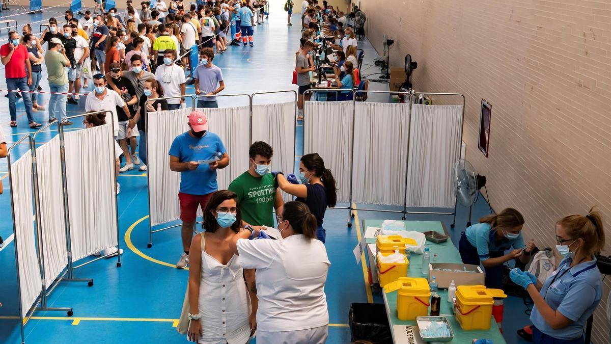 Multitud de jóvenes reciben la vacuna contra el coronavirus, este jueves en el pabellón municipal de Espartinas (Sevilla).
