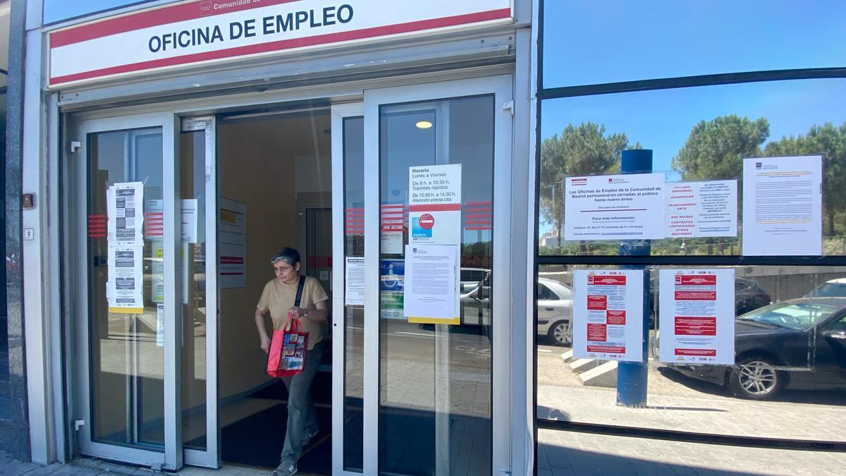 Una mujer sale por la puerta de una oficina del SEPE