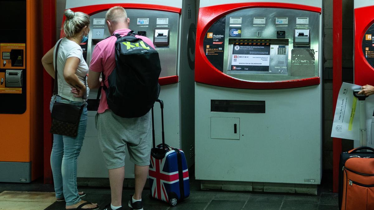 Una pareja de turistas británicos en la estación de Renfe de Plaza Cataluña en Barcelona.
