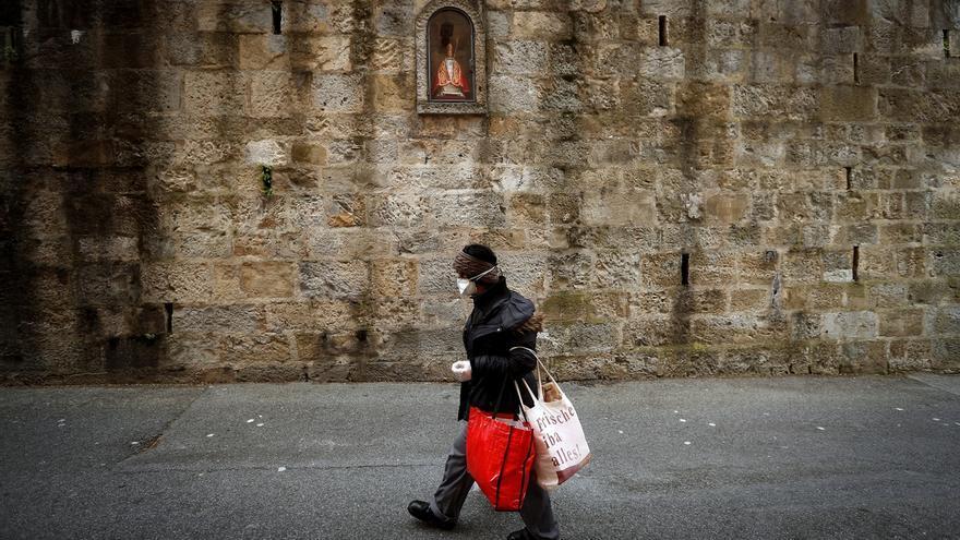 Una mujer pasa por delante de la hornacina de San Fermín en la cuesta de Santo Domingo de Pamplona, primer tramo del encierro de los Sanfermines.
