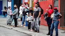 Personas con tapabocas esperan para tomar un bus de transporte público en Sao Paulo (Brasil).