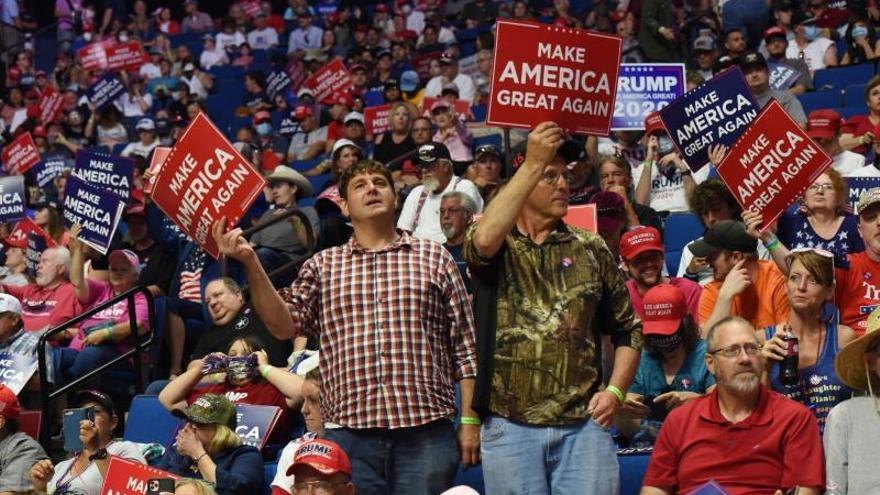 Simpatizantes de Donald Trump sostienen pancartas de apoyo en el Bank of Oklahoma Center en Tulsa, Oklahoma.