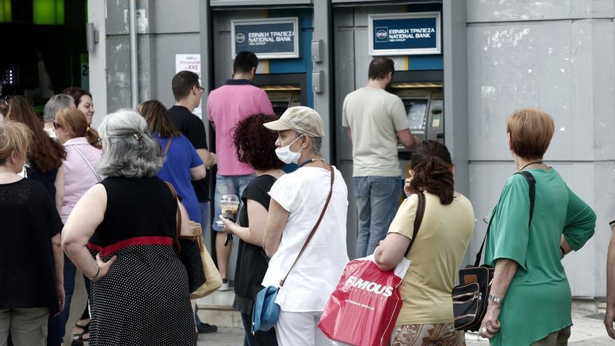 Ciudadanos griegos hacen cola ante un cajero automático el sábado 27 en un suburbio de Atenas. Panayiotis Tzamaros/Zuma Press