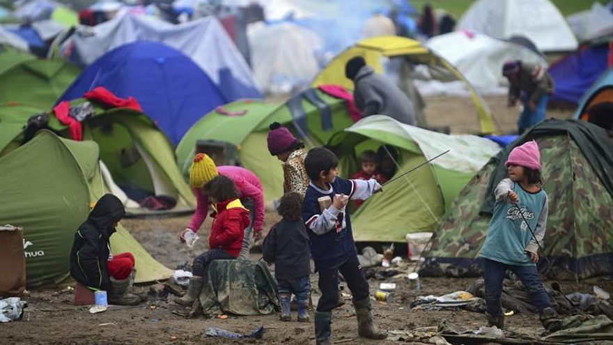 Varios niños juegan cerca de las tiendas de campaña mientras esperan en la frontera de Grecia y Macedonia.