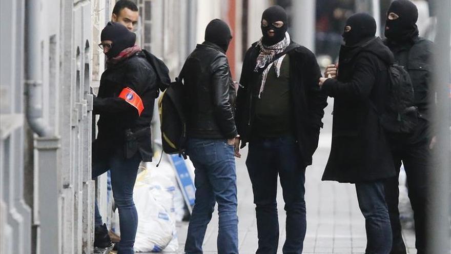 Inspectores de policía abandonan una residencia del distrito de Molenbeek en Bruselas (Bélgica).