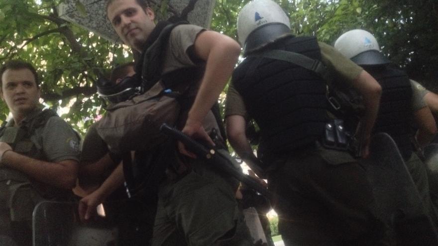 Policías protegiéndose de la lluvia bajo los árboles en la plaza Syntagma de Atenas en la manifestación del 'sí' del 30 de junio de 2015. / Andrés Gil