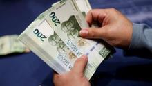 Una mujer muestra un billete de 200 pesos.