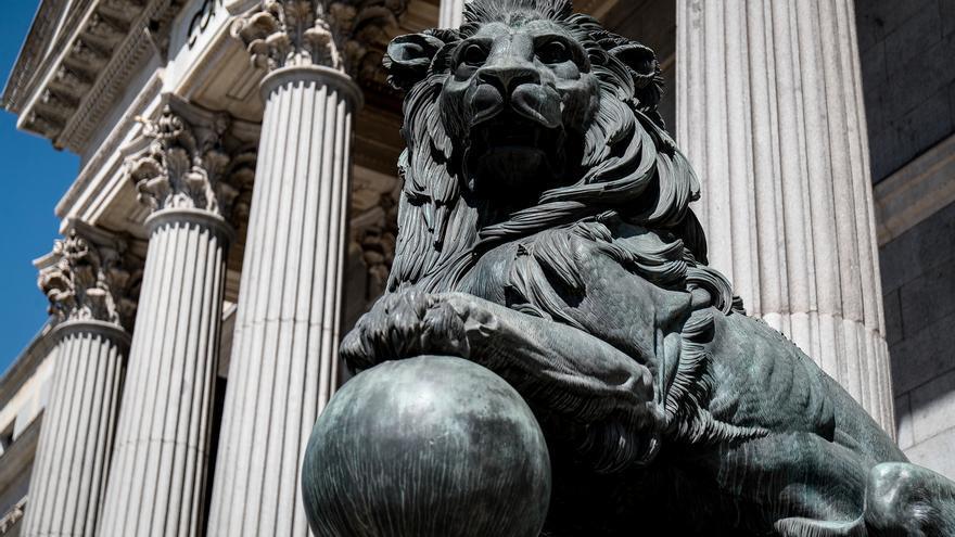 Archivo - Uno de los emblemáticos leones que se encuentran delante de la fachada del Congreso de los Diputados en la Plaza de las Cortes de Madrid.