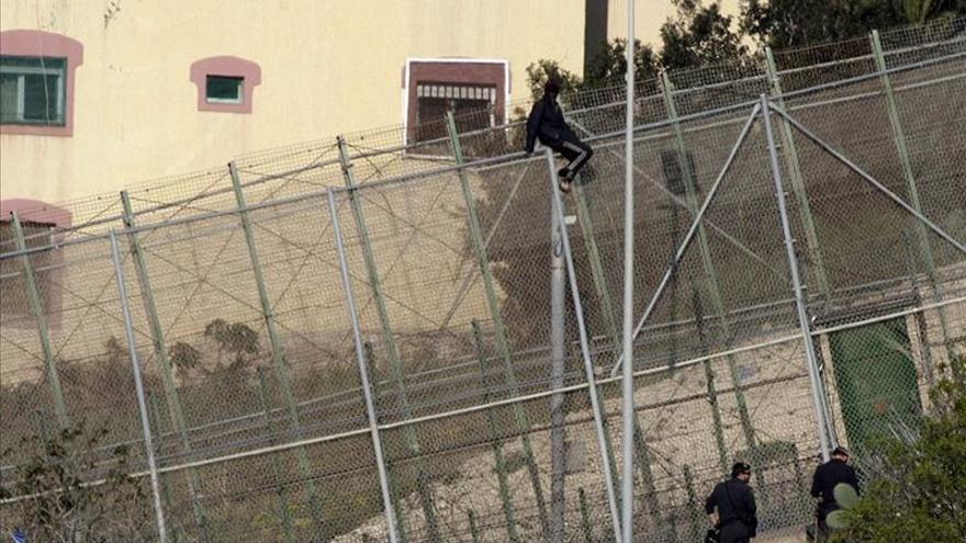 Una personas encaramada en lo alto de la valla de Melilla este miércoles en un intento de entrada./ EFE.