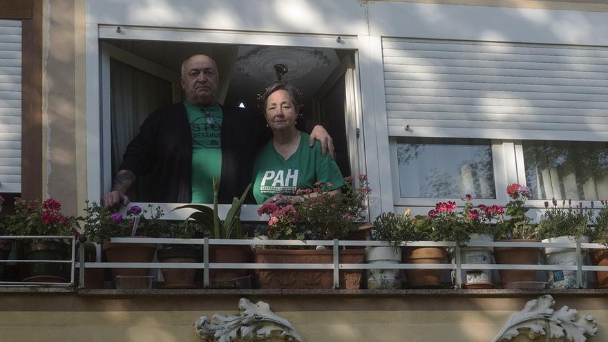 El matrimonio observa desde la ventana de su casa la salida de los periodistas de eldiario.es.