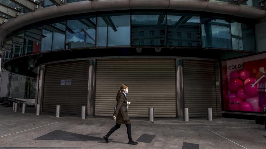 Una mujer camina con mascarilla por una calle de Madrid este domingo.