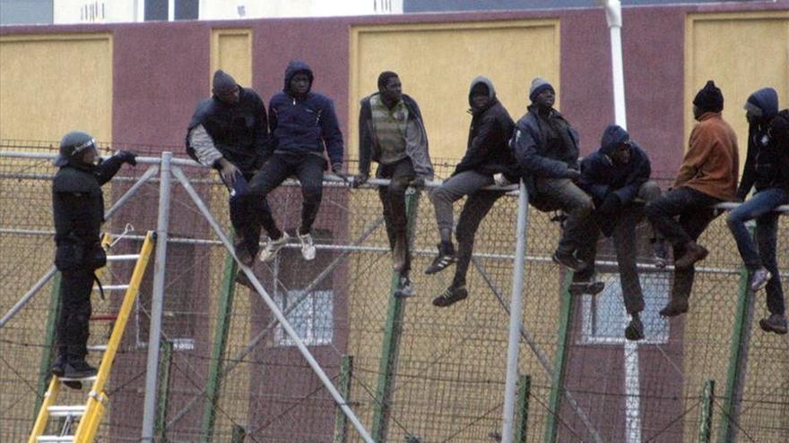 Unos 20 inmigrantes siguen en la valla de Melilla ante un fuerte despliegue. / EFE.