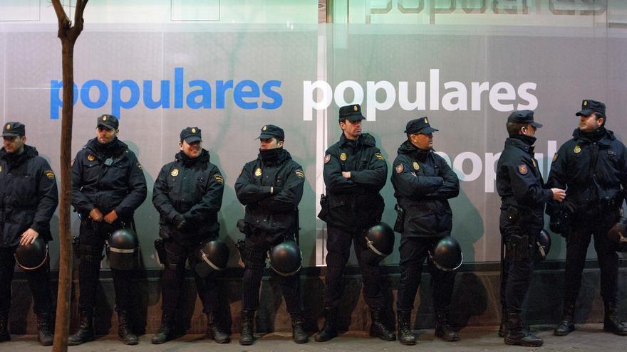 La Policia rodeando la sede del PP, a pesar de que los manifestantes se encontraban bastante lejos, entre dos cordones formados por vallas que han cortado la calle completamente durante tres horas / Álvaro Minguito