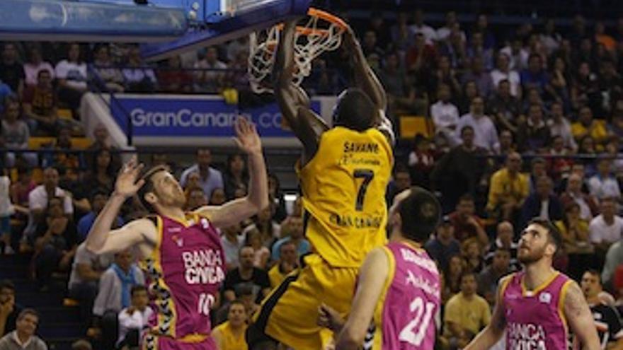 Savané machaca el aro ante la mirada de los jugadores del Banca Cívica. (cbgrancanaria.net)