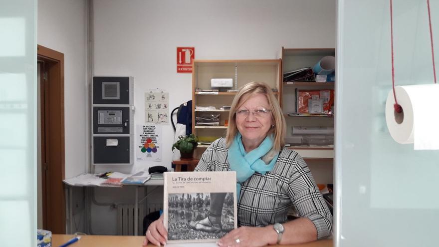 Una empleada de un colegio público muestra el libro de la tira de contar