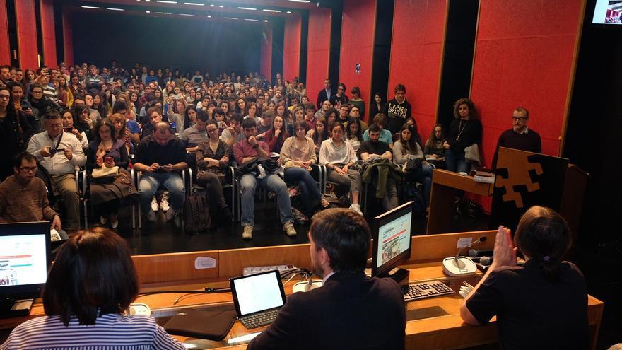Escolar, en el medio, se dirige a un salón de actos abarrotado.