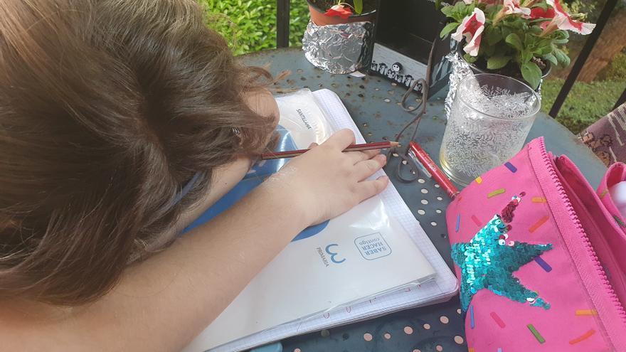 Niña derrotada por los deberes sobre su libro de matemáticas