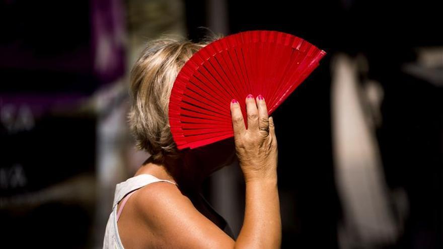 Una señora se tapa con un abanico en una calle del centro de Córdoba.