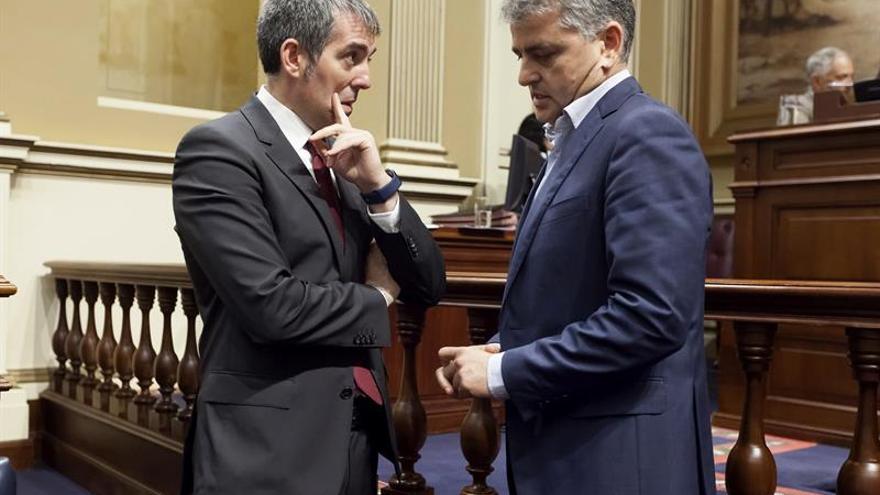 El Presidente del Gobierno de Canarias, Fernando Clavijo (i), conversa con el diputado del Grupo Nacionalista Canario, David de la Hoz (d), momentos antes del inicio del pleno del Parlamento de Canarias.