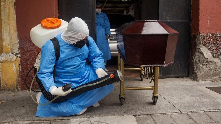 Un miembro de la Policía de Guatemala sanitiza el féretro de un hombre de 73 años, este lunes en Ciudad de Guatemala (Guatemala).