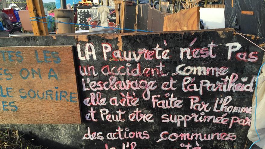 """Cartel en Calais: """"La pobreza no es un accidente, como la esclavitud o el apartheid ha sido creada por el hombre y puede ser suprimida por las acciones comunes de la humanidad"""" / José Bautista"""
