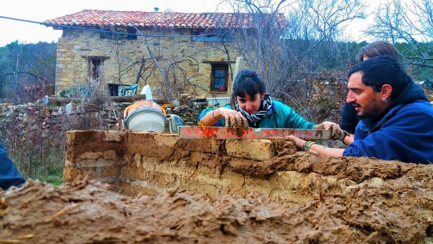 Miembros del movimiento okupa trabajando en la reconstrucción de una casa