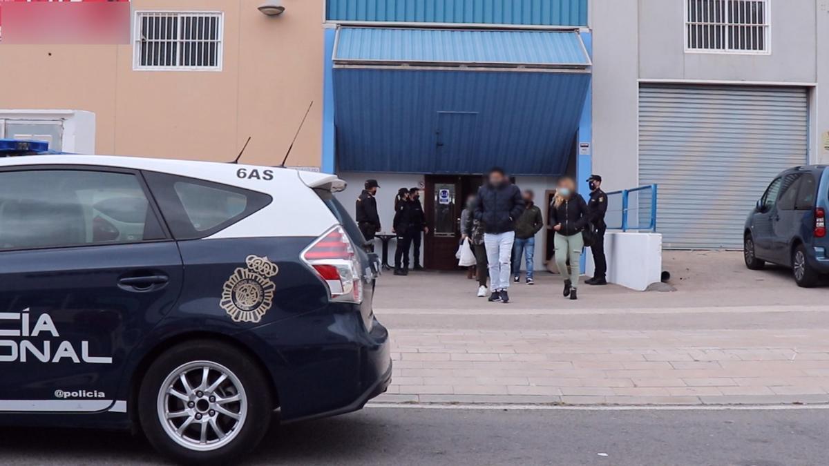 Agentes de la Policía desalojan la nave donde se estaba desarrollando la fiesta ilegal.