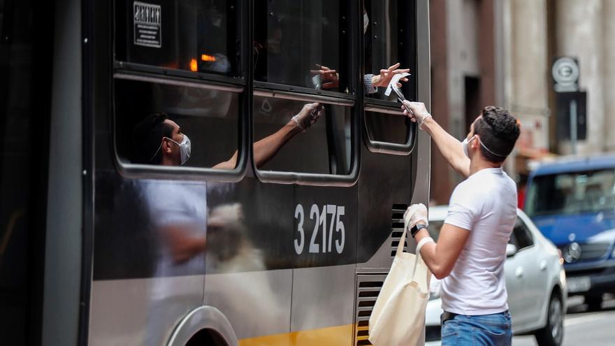 Voluntarios entregan hoy, miércoles 1 de julio de 2020, mascarillas durante una operación de Vigilancia Sanitaria para fiscalizar y advertir sobre el uso obligatorio para prevenir el contagio del COVID-19, en el centro de Sao Paulo (Brasil).