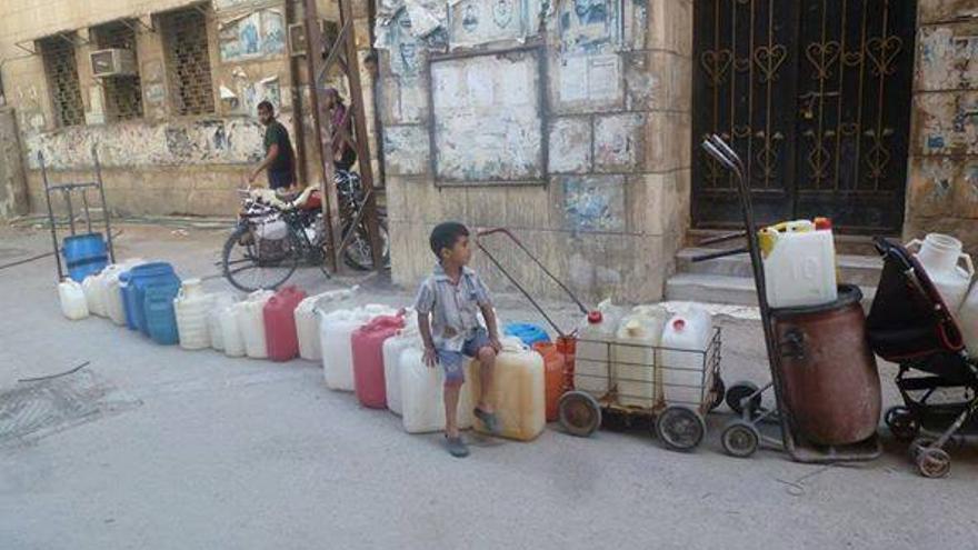 Un niño espera junto a una hilera de bidones vacíos en el barrio palestino de Yarmouk, asediado por el régimen. Fuente: página de la Revolución Siria en Facebook.