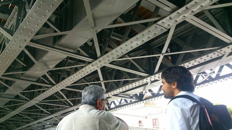 Un miembro de la Gestora junto con el consejero, observando la estructura metálica del puente que sí se pudo conservar.