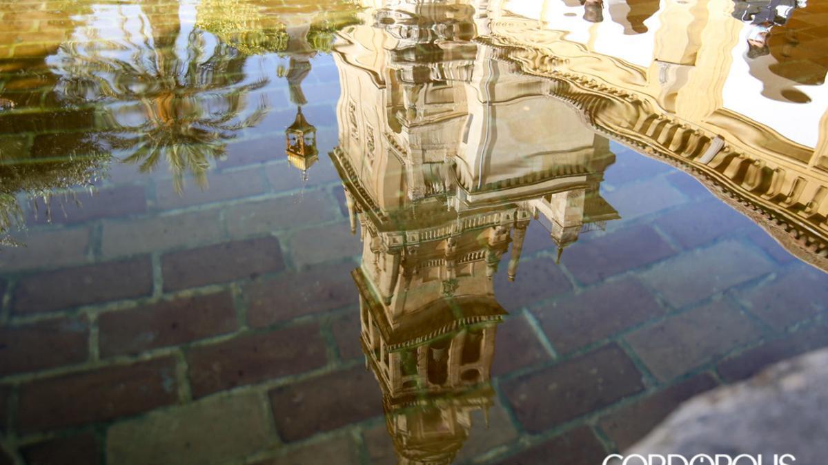 Torre alminar de la Mezquita Catedral reflejada en una fuente.