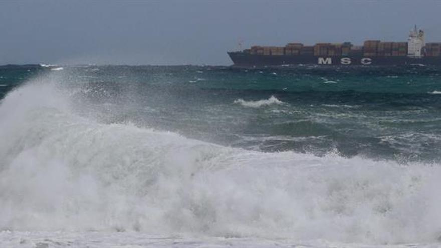 Un portacontenedores permanece fondeado en la bahía de Las Palmas de Gran Canaria mientras el fuerte oleaje azota el litoral