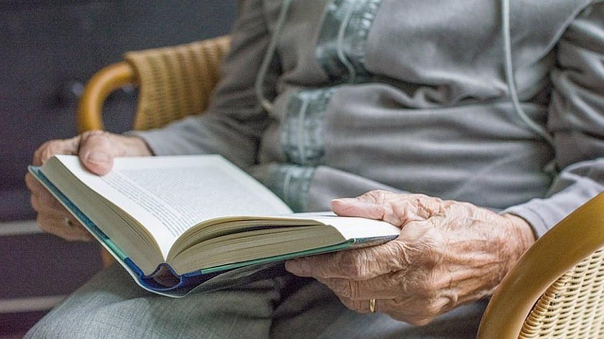Una persona mayor leyendo un libro