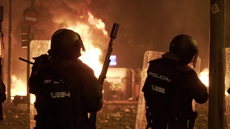 Antidisturbios ante un fuego en las calles de Barcelona en la quinta noche de protestas.