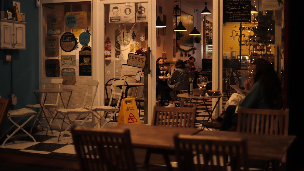Varias personas disfrutan del alumbrado navideño en una cafetería de La Laguna