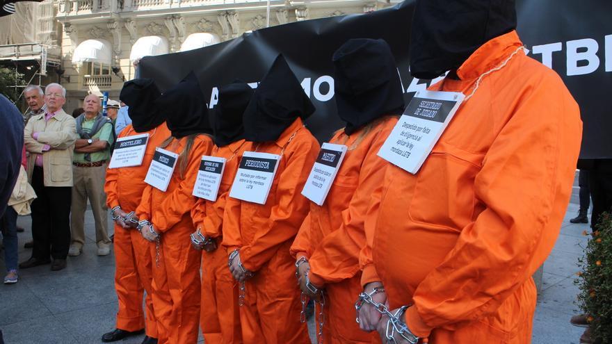 Seis personas encapuchadas y vestidas con monos naranjas han imitado a los presos de Guantánamo / MB